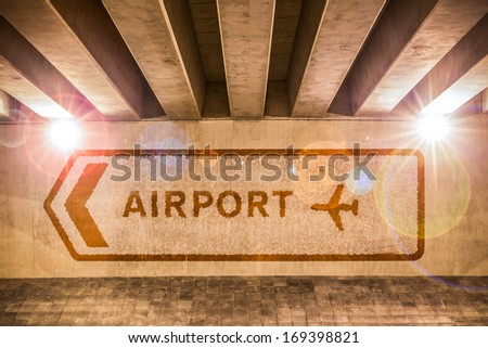 Directions towards Airport in English painted on a wall - stock photo