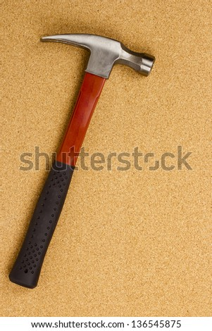 Directly above photograph of a hammer on a brown background.
