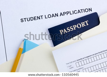Directly above photograph of a student loan application and a passport. - stock photo