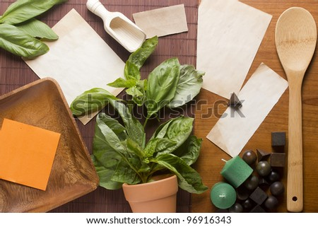 Directly above photograph of basil leaves, papers, and decorative objects for herbal medicine or culinary topics. Add your text to the papers.