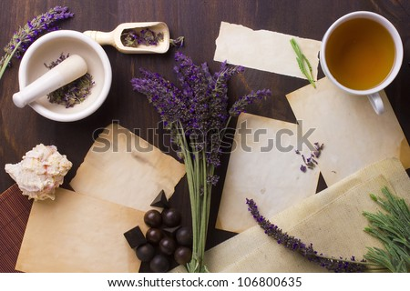 Directly above photograph of lavender flowers, papers, and decorative objects to portray the topic of alternative medicine. Add your text to the papers. - stock photo