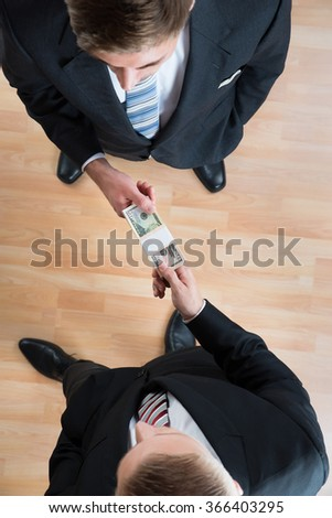 Directly above shot of businessman bribing colleague in office - stock photo