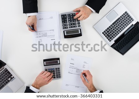 Directly above shot of businessmen calculating finance at desk in office - stock photo