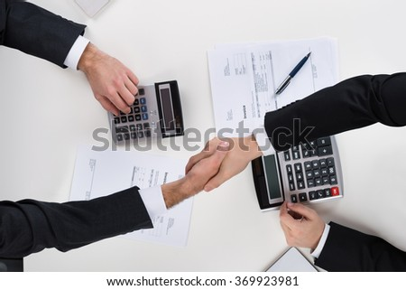 Directly above shot of businessmen shaking hands while calculating finance at desk - stock photo