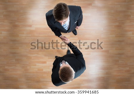 Directly above shot of businessmen shaking hands while standing on wooden floor in office