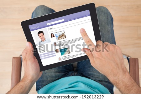 Directly above shot of man surfing on social site using digital tablet at home - stock photo