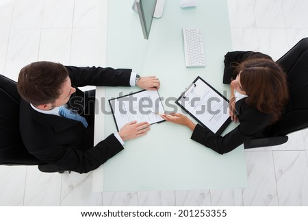 Directly above shot of young businesswoman interviewing male candidate in office - stock photo