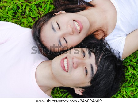 Directly above shot of young couple lying on grass in park - stock photo