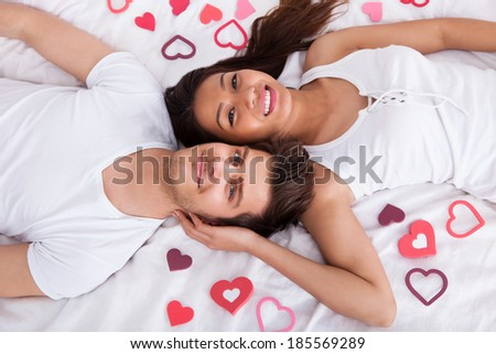 Directly above shot of young couple lying on mattress at home - stock photo
