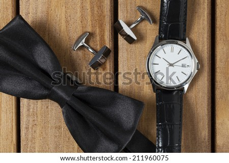 Directly above view of a old wooden table, bowtie cufflinks and wristwatch on it - stock photo