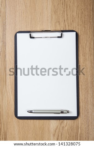 Directly above view of a wooden table , papers and a pen on it  - stock photo