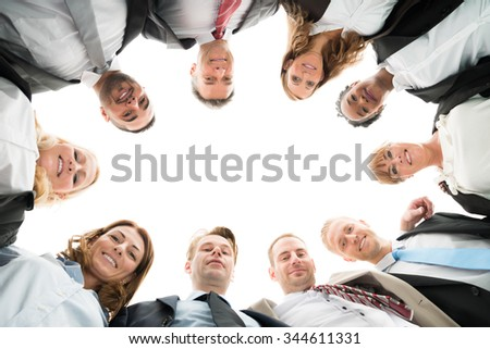 Directly below portrait of confident business team standing in huddle against white background - stock photo