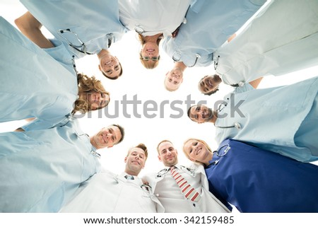 Directly below portrait of confident medical team standing in huddle against white background - stock photo