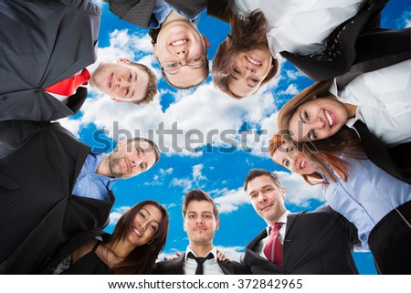 Directly below portrait of diverse business team forming huddle against sky