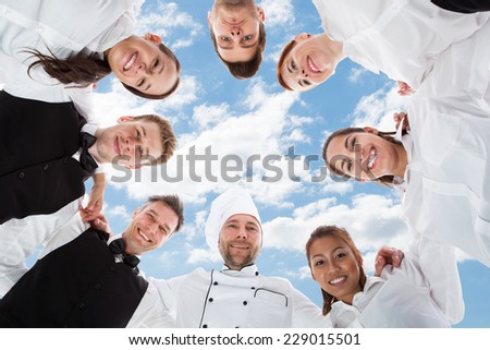 Directly below portrait of happy chef and waiters standing in huddle against sky - stock photo