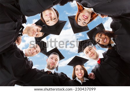 Directly below portrait of happy multiethnic graduates forming huddle against sky - stock photo