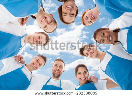 Directly below shot of diverse professional cleaners standing in huddle against sky - stock photo