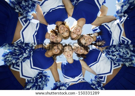 Directly below shot of happy cheerleaders forming huddle against sky - stock photo