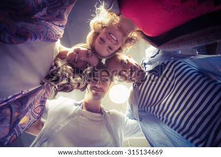 Directly below shot of happy colleagues in huddle at office - stock photo