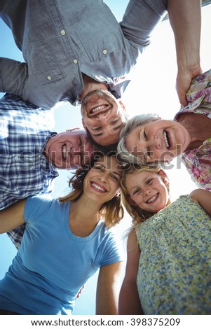Directly below shot of happy family forming huddle in back yard against sky - stock photo
