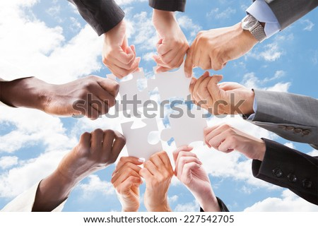 Directly below shot of multiethnic business people assembling jigsaw puzzle against sky - stock photo