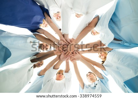 Directly below shot of multiethnic medical team stacking hands over white background - stock photo