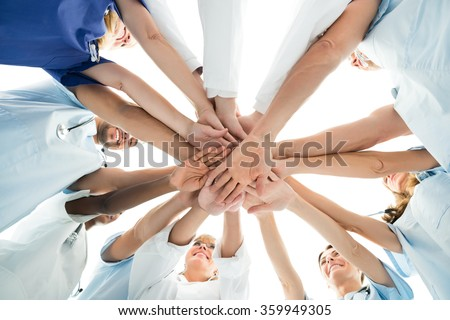 Directly below shot of multiethnic medical team stacking hands over white background
