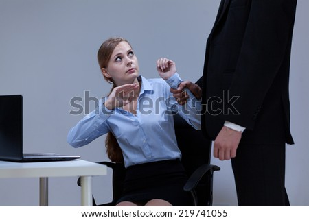 Director bullying his young attractive employee in the office - stock photo