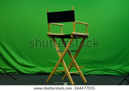 Director's chair in front of green screen  - stock photo