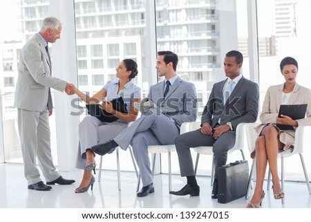 Director welcoming businesswoman sat in a waiting room - stock photo