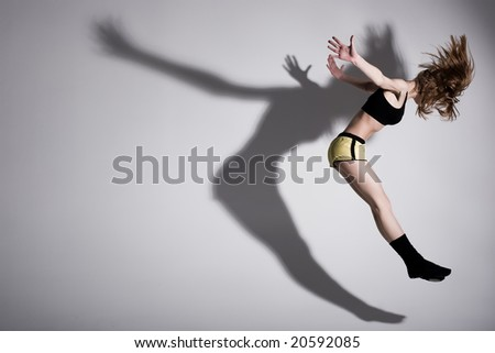 dirl is jumping up with her shadow - stock photo