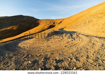 Dirt mountain road crossing alpine slopes and meadows covered by yellow grass in autumn season at sunset. Wide angle view of hairpin curve. - stock photo