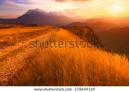 Dirt road and mountain grass towards the sun - stock photo