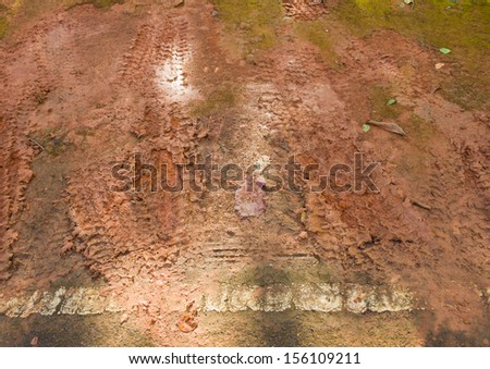 Dirt road and wheel lines on the mud - stock photo