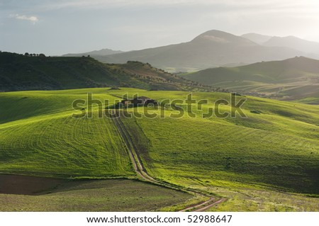 dirt road crosses grassland with a old hut against cloudy sky at the twilight - stock photo