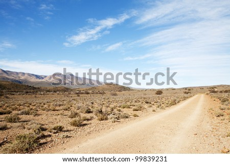 Dirt road in arid region leading away from viewer