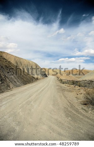 Dirt Road in Desert - stock photo