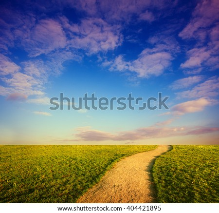 Dirt road in grassy field, sky and clouds over horizon