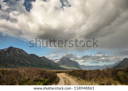 Dirt road in remote Yukon Territory with a summer storm clouds and rainbow.