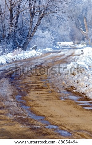 Dirt road in winter snow and frost - stock photo