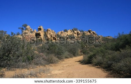 Dirt road leading past sandstone outcrops, Thousand Oaks, CA - stock photo