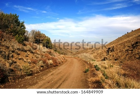 Dirt road leading through a canyon in the high desert, California - stock photo
