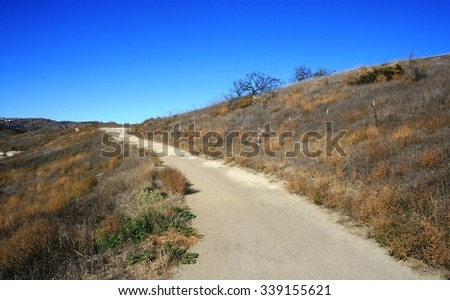 Dirt road leading up a hillside, San Fernando Valley, CA - stock photo