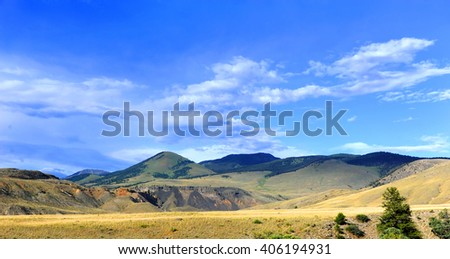 Dirt road passes through Paradise Valley in Wyoming.  Road has distant view and panorama of the Absaroka Mountains. - stock photo