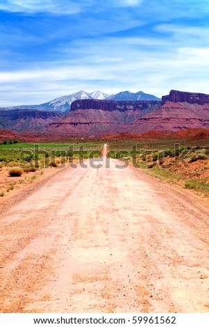 Dirt Road to Mountains - stock photo