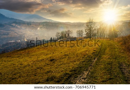 dirt road to village down the hill. trees on hillside and village in valley in autumnal countryside landscape in evening light