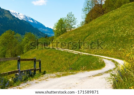 Dirt road with a view over snowy mountain in Switzerland.
