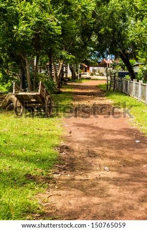 Dirt track through village - stock photo