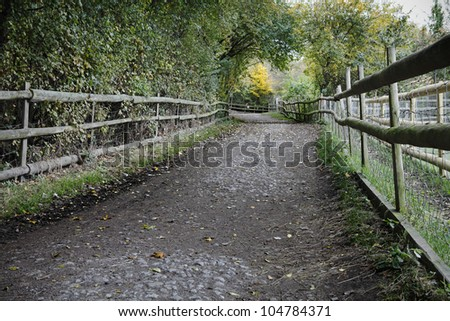 Dirt trail through an urban farmland in Mudchute Park, London, England. - stock photo