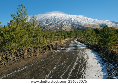 dirt trail to the volcano Etna snow covered, Sicily - stock photo